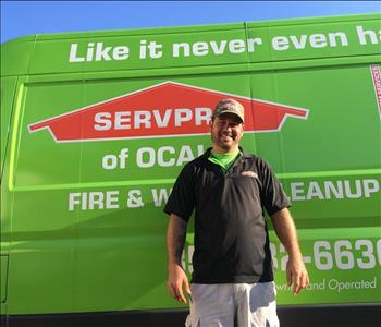 male employee standing next to a SERVPRO branded green truck