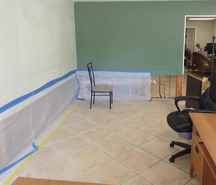 Picture of remediated office with drywall cut out and covered with visqueen