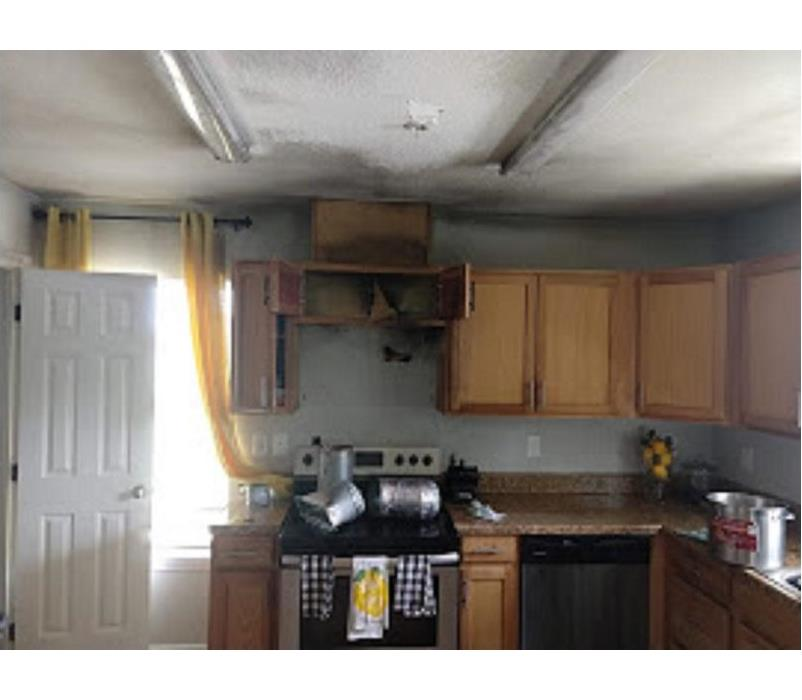 Picture of a kitchen that stove caught on fire damaging cabinets and wall.
